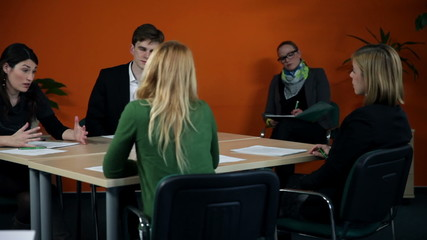 young employees who have important business meeting session in an orange colored office