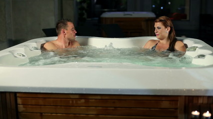 young couple having conversation and spending night time in jacuzzi on romantic date