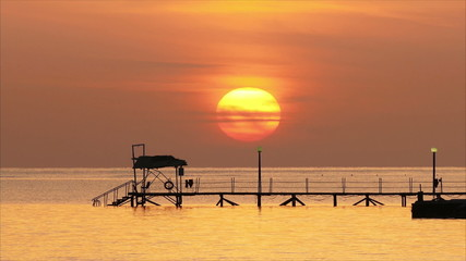 beautiful sunrise over pier in sea - filmed at telephoto lens, t