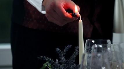 waiter who lights candle before bringing romantic dinner