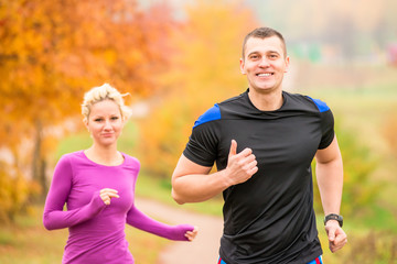 cheerful young athletes jogging autumn morning