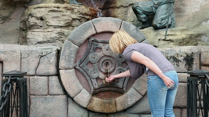 Woman drinking water from fountain