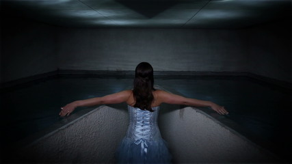 Woman in a beautiful dress touching water surface and creating pattern reflectin on ceiling
