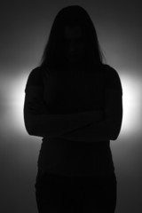 Silhouette of teenage girl with arms crossed