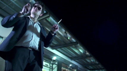 Man with sunglasses playing the aridrums with drum sticks at night in slow-mo