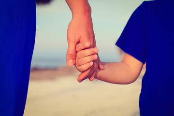 mother and son holding hands on the beach