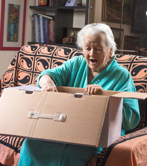 Happy old woman holding a large cardboard box
