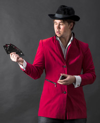 Young magician in hat with cards