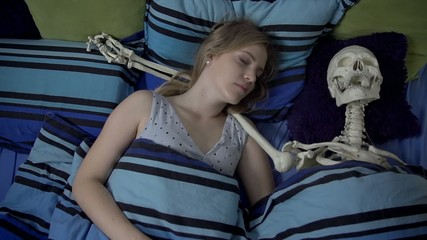 Woman laying in the bed with skeleton