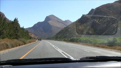 Driving tar road with mountains