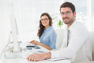 Portrait of smiling team with glasses at desk
