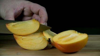 Slicing persimmon into thin slices in slow motion