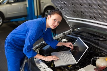 Mechanic using laptop on car