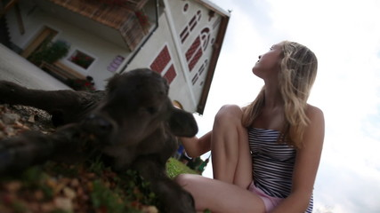 HD1080p: Teenage girl caressing calf in front of the house