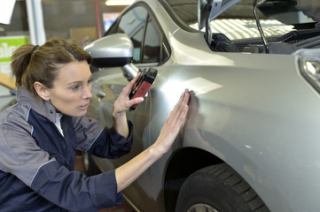 Woman technician working in auto bodywork shop