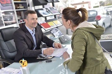 Car dealer editing purchase agreement to buyer