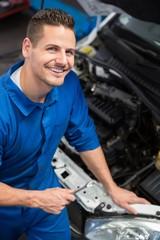 Smiling mechanic looking up at camera