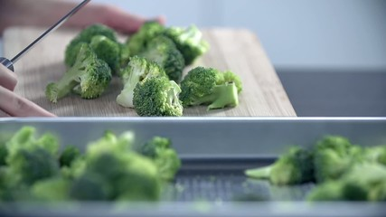 Putting pieces of broccoli into a tray