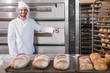 Leinwanddruck Bild - Happy baker leaning on professional oven