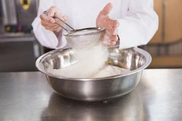 Baker sieving flour into a bowl