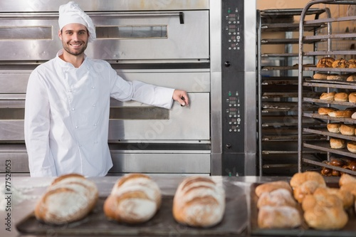 Happy baker leaning on professional oven - 77524053