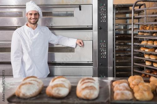 Leinwanddruck Bild Happy baker leaning on professional oven