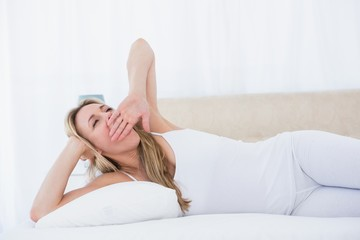 Blonde woman lying in bed yawning