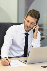 Cheerful Businessman on mobile phone in office