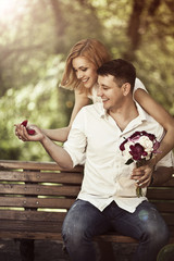 Love and wedding concept. Young happy couple sitting in the park