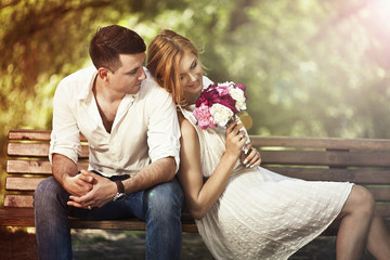 Young beautiful couple sitting in the park and man proposing wo