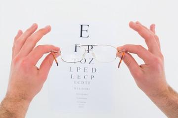 Hands holding glasses for eye test