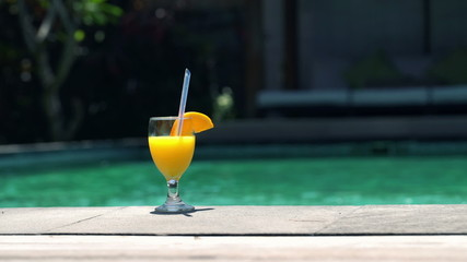 Summer drink with straw by the swimming pool