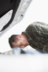 Upset businessman leaning on his car