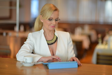 Successful and atractive middle aged woman working on tablet pc