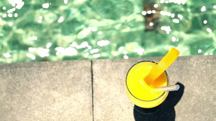 Summer drink with straw by the swimming pool, top view