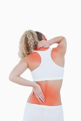 Blonde woman touching her neck and back as an indication of pain