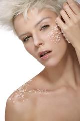 blond model applying a scrub treatment on the body an face