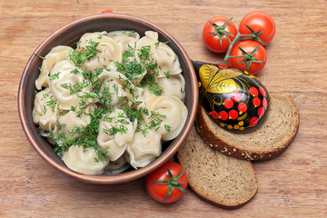 Russian dumplings with fennel, cherry tomatoes and bread on a wo