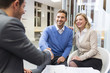 Young couple shaking hand real-estate agent in agency office - 77528255