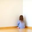 Sad little girl sitting in a corner