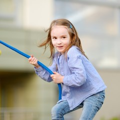 Little preschooler girl having fun with a rope