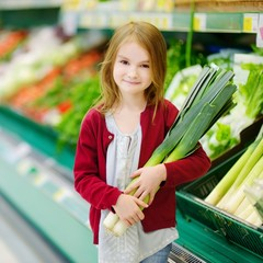 Little girl choosing a leek in a store
