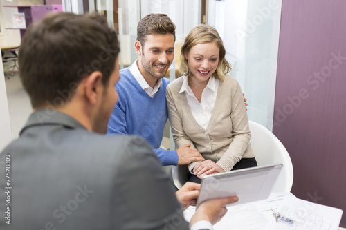 Couple meeting real-estate showing a house project on tablet pc - 77528809