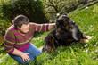 behinderte Frau streichelt Hund auf einer Wiese