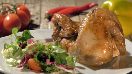 roast chicken with salad on white plate rotating