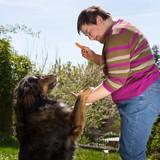 Geistig behinderte Frau füttert ihren Hund