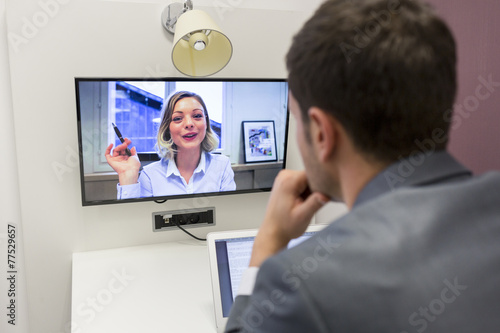 Businessman on video conference with her colleague in office job - 77529657