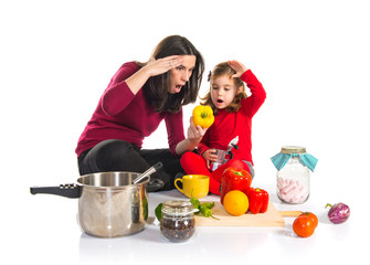 Surprised mother and daughter playing cooking