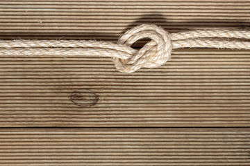 Wooden background with rough rope