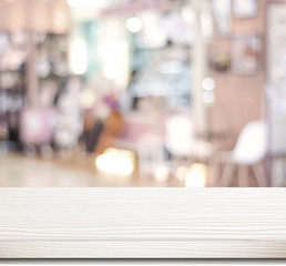 Empty white table and blurred cafe with bokeh light background
